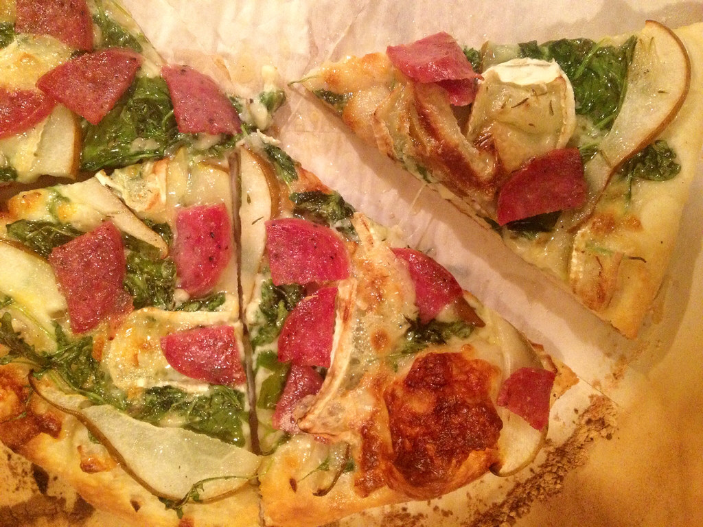 Pizza with arugula, pear, salami, and Brie.
