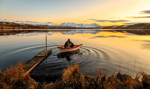 newzealand sky mountain lake water grass sunrise dawn golden boat fisherman glow ripple canterbury nz southisland lakealexandrina snowcappedmountain mackenziedistrict fabphotography fernandezbarrett