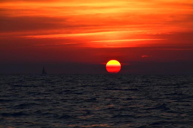 Preciosa puesta del sol al norte de Menorca con el sol como una enorme bola de fuego en Catamarán