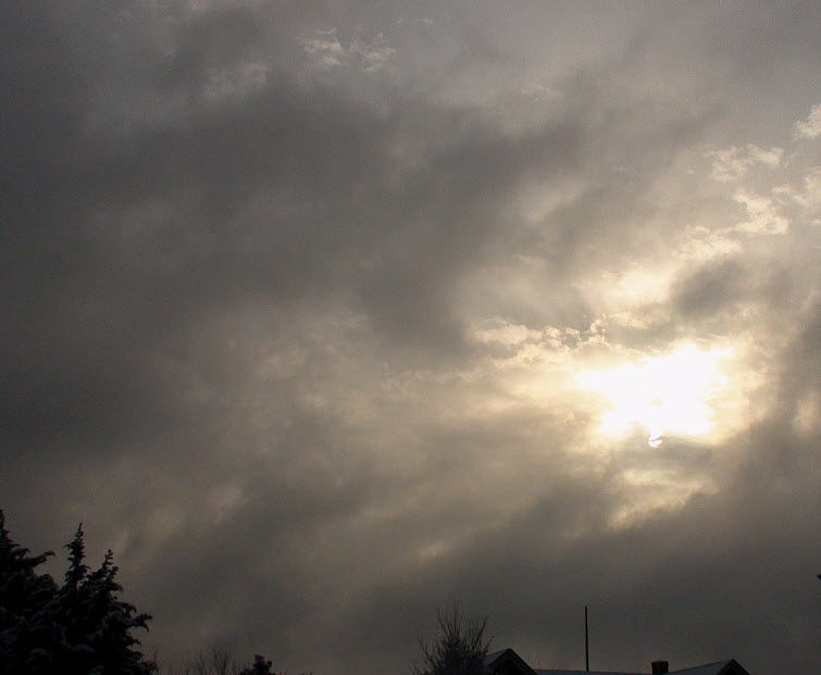sun through gray puffy clouds