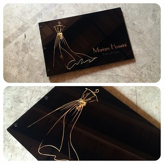 Custom fashion design portfolio book with engraved color fill and gold foil treatment on glossy black acrylic