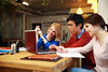 Happy students doing homework with laptop together
