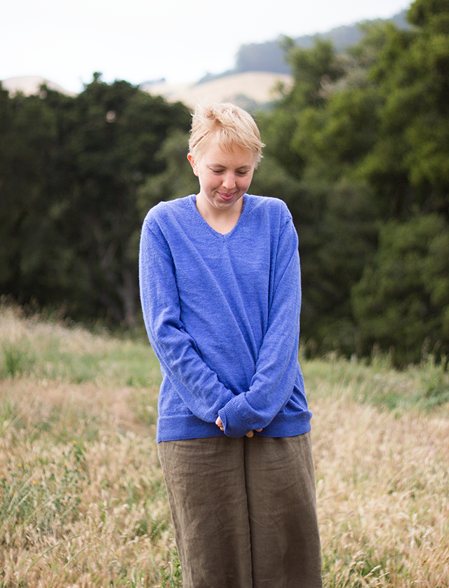 periwinkle blue wool sweater, brown linen trousers, forest background