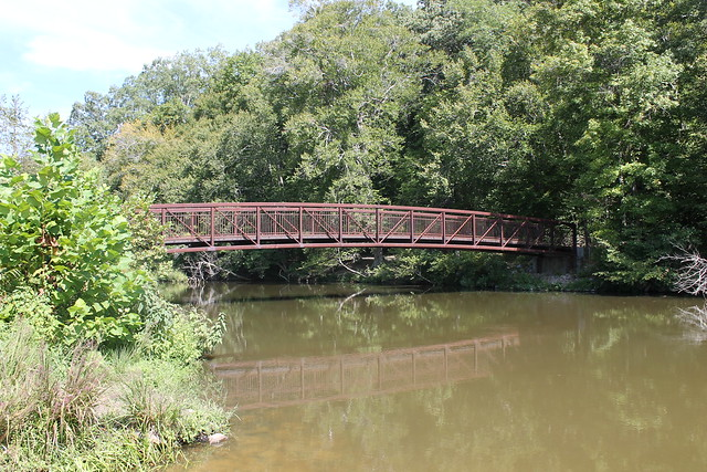 The Pedestrian Bridge Crosses Over Swift Creek Lake Leading To The Forest Exploration Trail