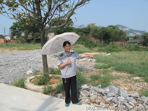 陳利芳女士手指方向的灰色屋頂就是她家,與廠區僅一牆之隔。