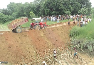 A tractor dumps soil on to the embankment