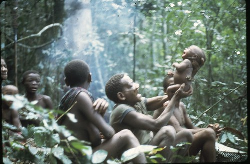 Mbuti baby in forest with camp