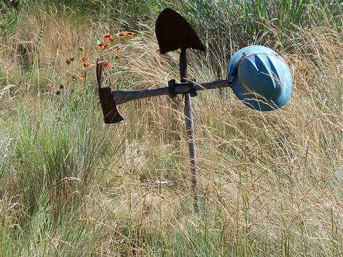 A cross made of a hard hat, shovel and Pulaski used by wildland firefighters stands at the Wildland Firefighters Monument in Boise, Idaho. (U.S. Forest Service)