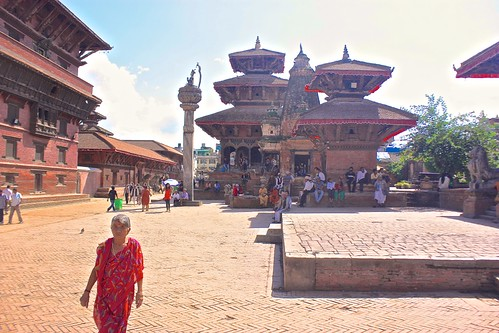 a woman walks in Durbar Square Patan