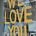 The words 'We Love You' written on a shop window