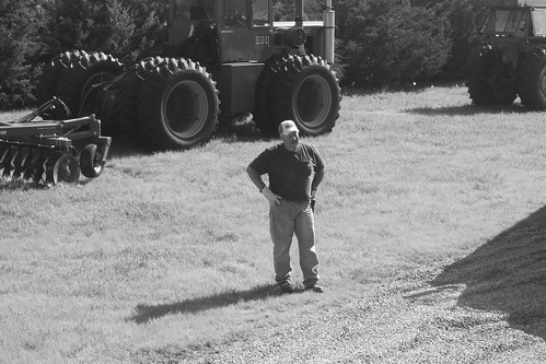 Dad watches as Brandon drives the combine up on to the trailer.