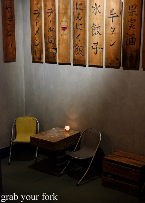 Tiny bar chairs beneath the wooden menu boards at Chaco Bar, Darlinghurst