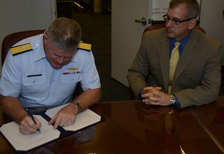 Rear Adm. Fred Midgett, commander Coast Guard 9th District, signs a mutual training agreement between the Coast Guard and the Lake Carriers' Association as Jim Weakley, president of LCA, looks on at the Coast Guard 9th District's headquarters in Cleveland, Aug. 11, 2014. The MTA will allow Coast Guard marine inspectors to join a vessel's crew while underway and act as a riding observer, giving the inspectors a practical knowledge of the performance and operating characteristics of the vessels, equipment, the waterways they transit and the vessel crews. U.S. Coast Guard photo by Petty Officer 2nd Class Levi Read