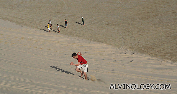 A boy running up a sand dune slope
