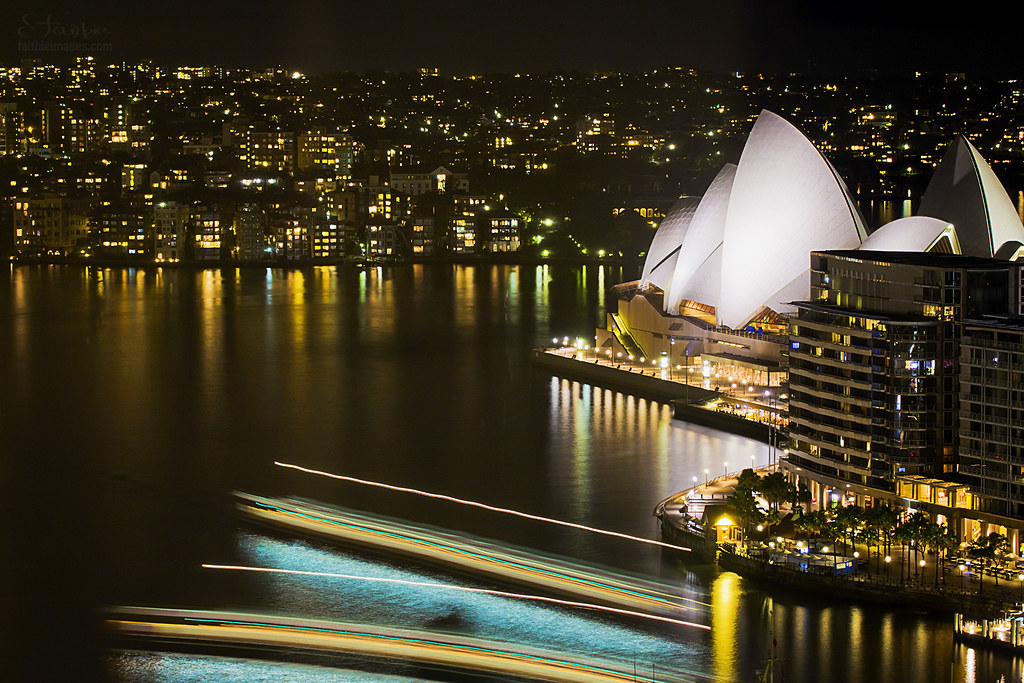 Shining Sydney Opera House by night, with ferry light trails