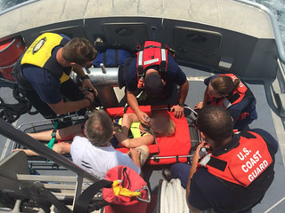 Atlantic Beach, N.C., Fire Dept. EMT (left) and Coast Guard Station Fort Macon crewmembers aboard a 47-foot Motor Lifeboat (MLB) provide medical assistance for a woman suffering from seasickness south of Atlantic Beach, N.C., July 20, 2014.  A 25-foot Response Boat-Small crew transported and trasferred EMTs to the MLB crew who had taken the woman aboard after she began to lose conciousness on a 27-foot pleasure craft.  U.S. Coast Guard photo courtesy of Station Fort Macon