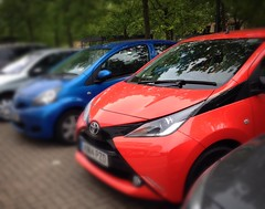 Brand new burnt orange coloured Aygo parked next to an older Aygo (I got way too excited about this)!