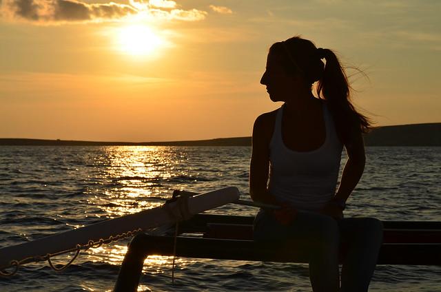 Diana al atardecer dirigindo el catamarán por Menorca