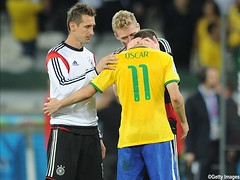 BELO HORIZONTE, BRAZIL - JULY 08: Oscar of Brazil is consoled by Andre Schurrle of Germany following the 2014 FIFA World Cup Brazil Semi Final match between Brazil and Germany at Estadio Mineirao on July 08, 2014 in Belo Horizonte, Brazil.  (Photo by Chri