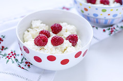 Cottage cheese with raspberry in white bowl of pea…