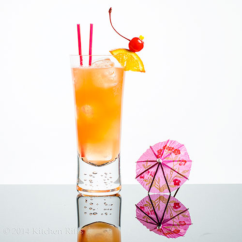 Straits Sling Cocktail with orange and cherry garnish