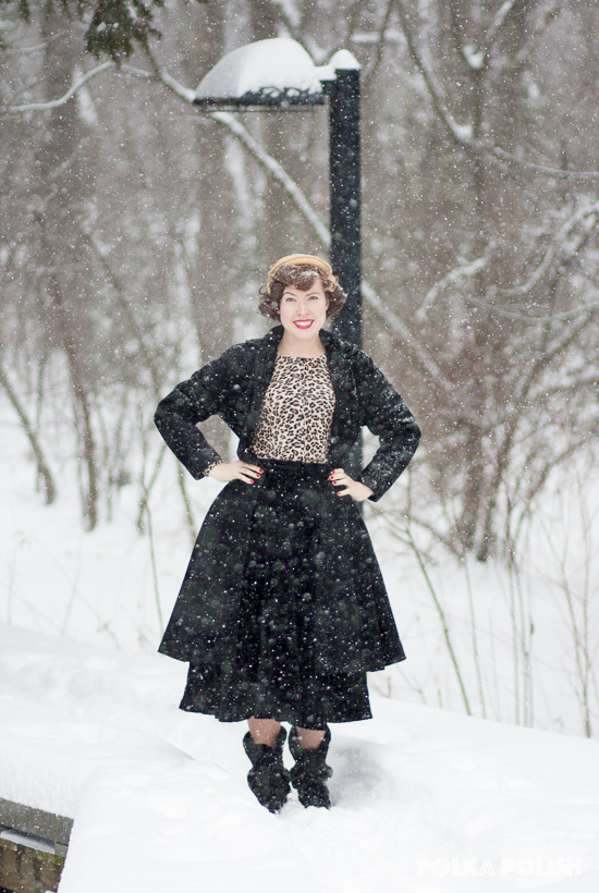 1950s inspired outfit with a black coat and skirt paired with a leopard print sweater and matching hat on a snowy winter day