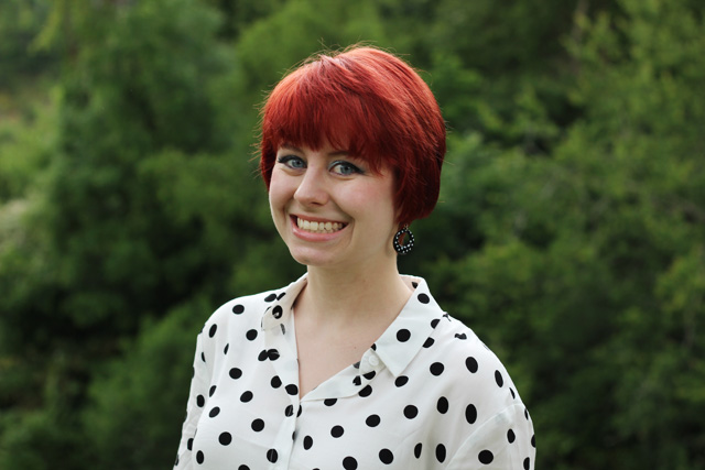 Short red hair, polka dot top, & polka dot earrings