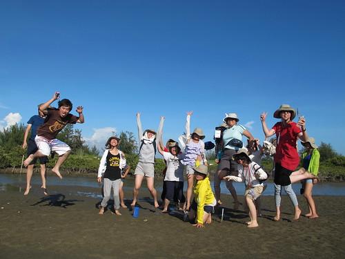 志工們搭竹筏遊潟湖,在沙洲上開心合影