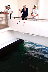 U.S. Secretary of State John Kerry and U.S. Navy Admiral Samuel Locklear, Commander of the U.S. Pacific Command, throw rose petals into a well at the USS Arizona memorial site in Pearl Harbor, Hawaii, on August 13, 2014, after the two laid a wreath at the famed World War II site. It followed a regional military briefing coming at the conclusion of an around the world trip that included stops in Burma, Australia, and the Solomon Islands. [State Department photo/ Public Domain]