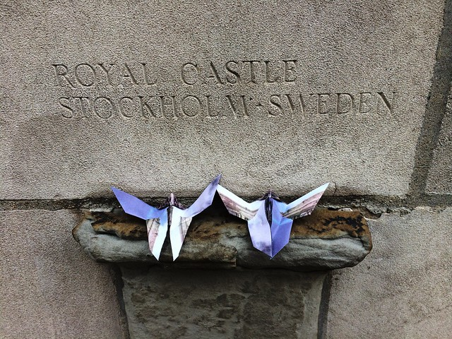 Two origami butterflies on the Tribune Tower rock ledge