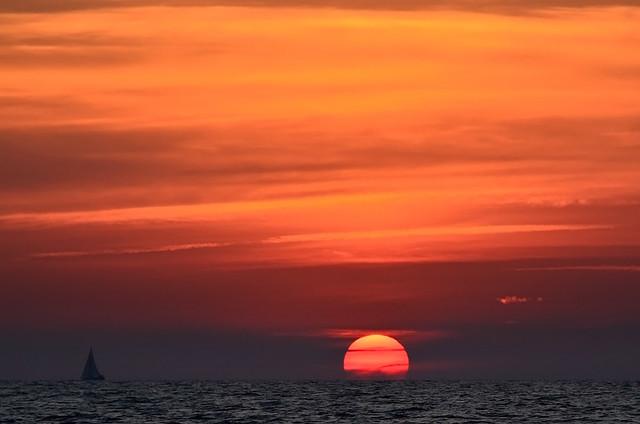 El cielo de Menorca ardiendo en rojos, naranjas y luces junto a barcos y el Mediterráneo