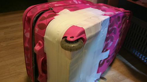 Pink suitcase with plenty of tape