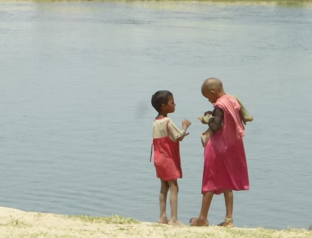 Two young girls converse on the banks of the river