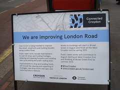 "A sign headed ""We are improving London Road"" with a Connected Croydon logo in the top right-hand corner and logos for Croydon Council, the Mayor of London, and Transport for London at the bottom."