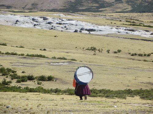 lady carrying a drum in the middle of no where