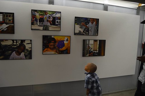 Brenda Muhammad's grandson looks at his grandmother's photo display, including two images featuring him, during the opening reception held Sept. 11, 2014.