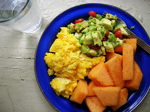 cheesy scrambled eggs, avocado tomato salsa, chili-salted cantaloupe, and water