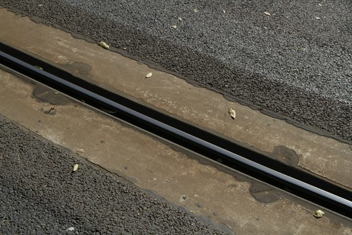 Detail of the central guide rail embedded in concrete and asphalt