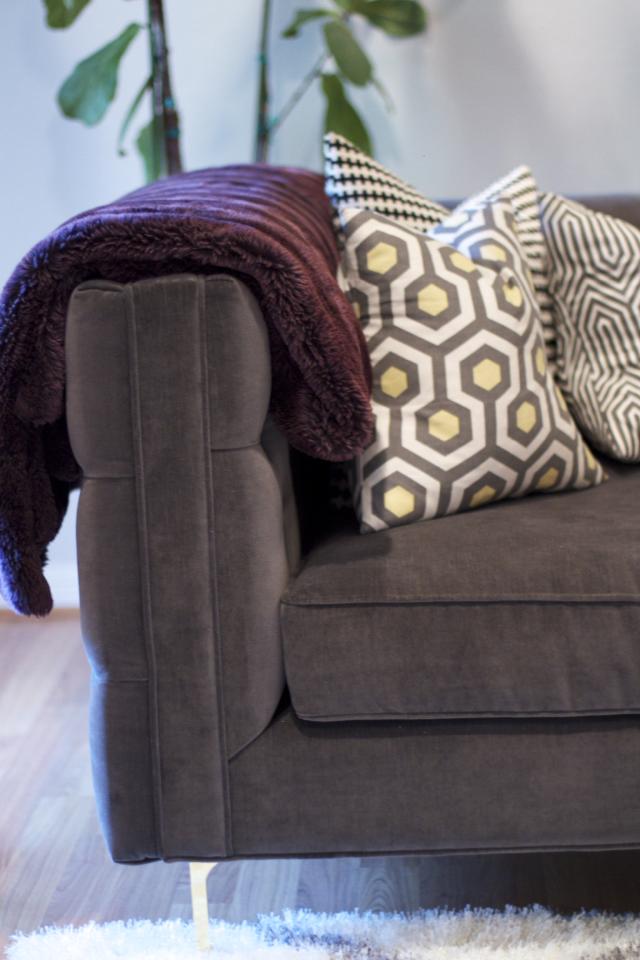 grey velvet tufted sofa with brass legs