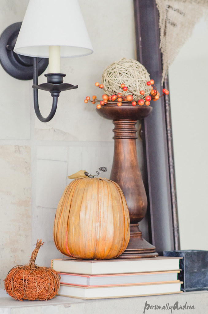 Fall mantel vignette with books, woodturned candlestick, faux mini-pumpkins, berry sprigs and mirror | personallyandrea.com
