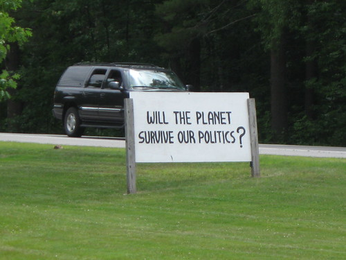 photo of a sign reading Will The Planet Survive Our Politics with a black SUV passing behind