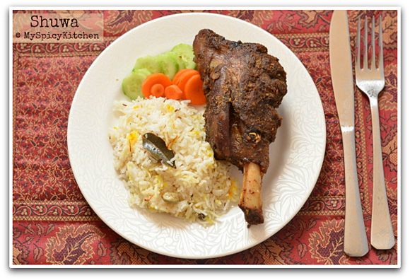 Omani lamb shank on a plate with some salad and flavored rice