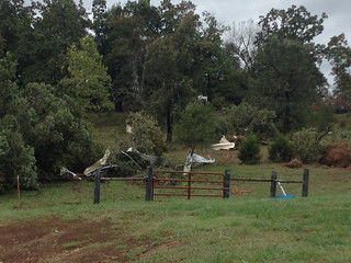 Picture of pieces of a carport scattered across a field