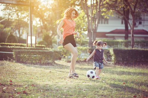 Young mother with daughter playing soccer