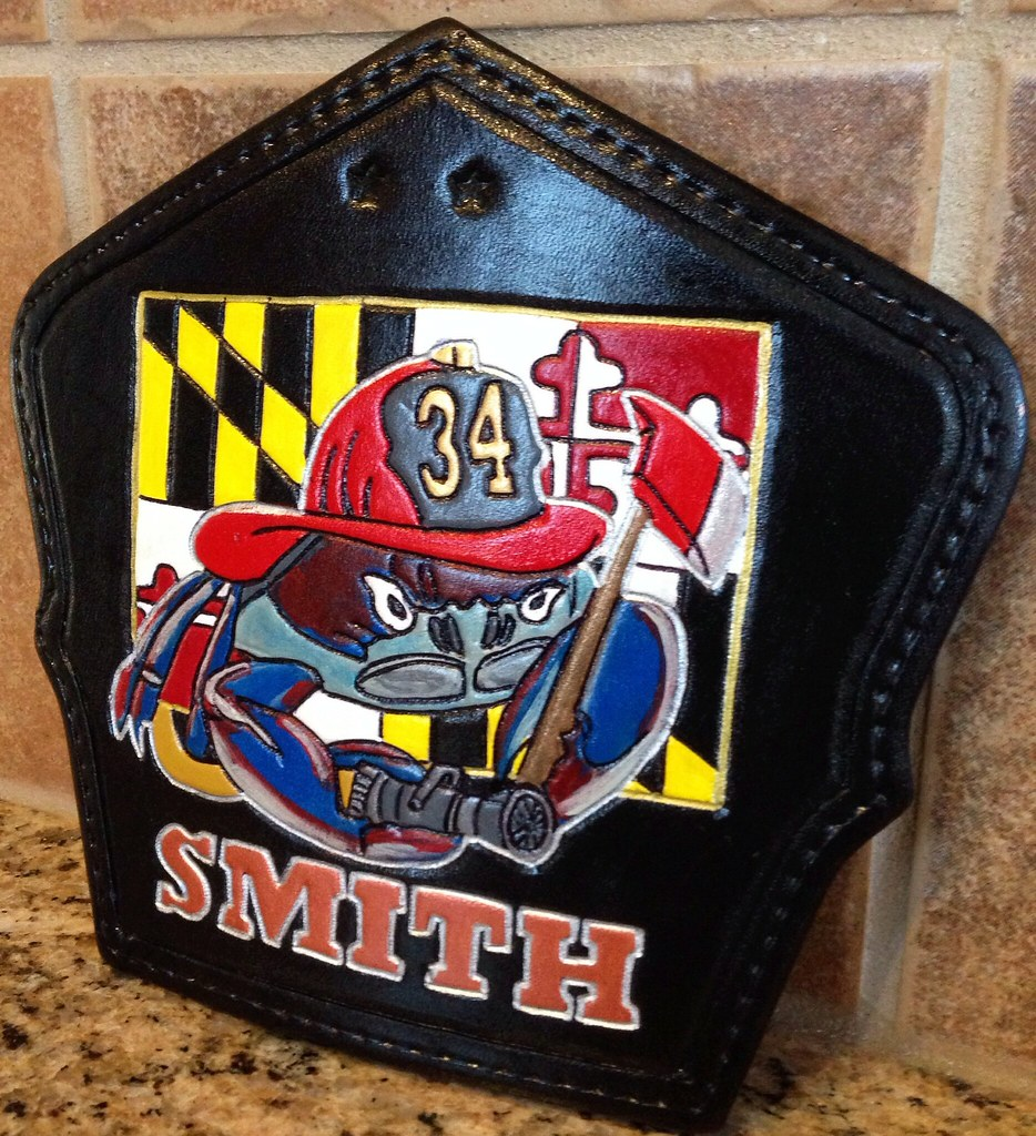 Wagon fire helmet shield. Maryland blue crab with axe and hose line over an MD flag