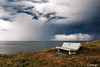 bench on cliff with storm over sea