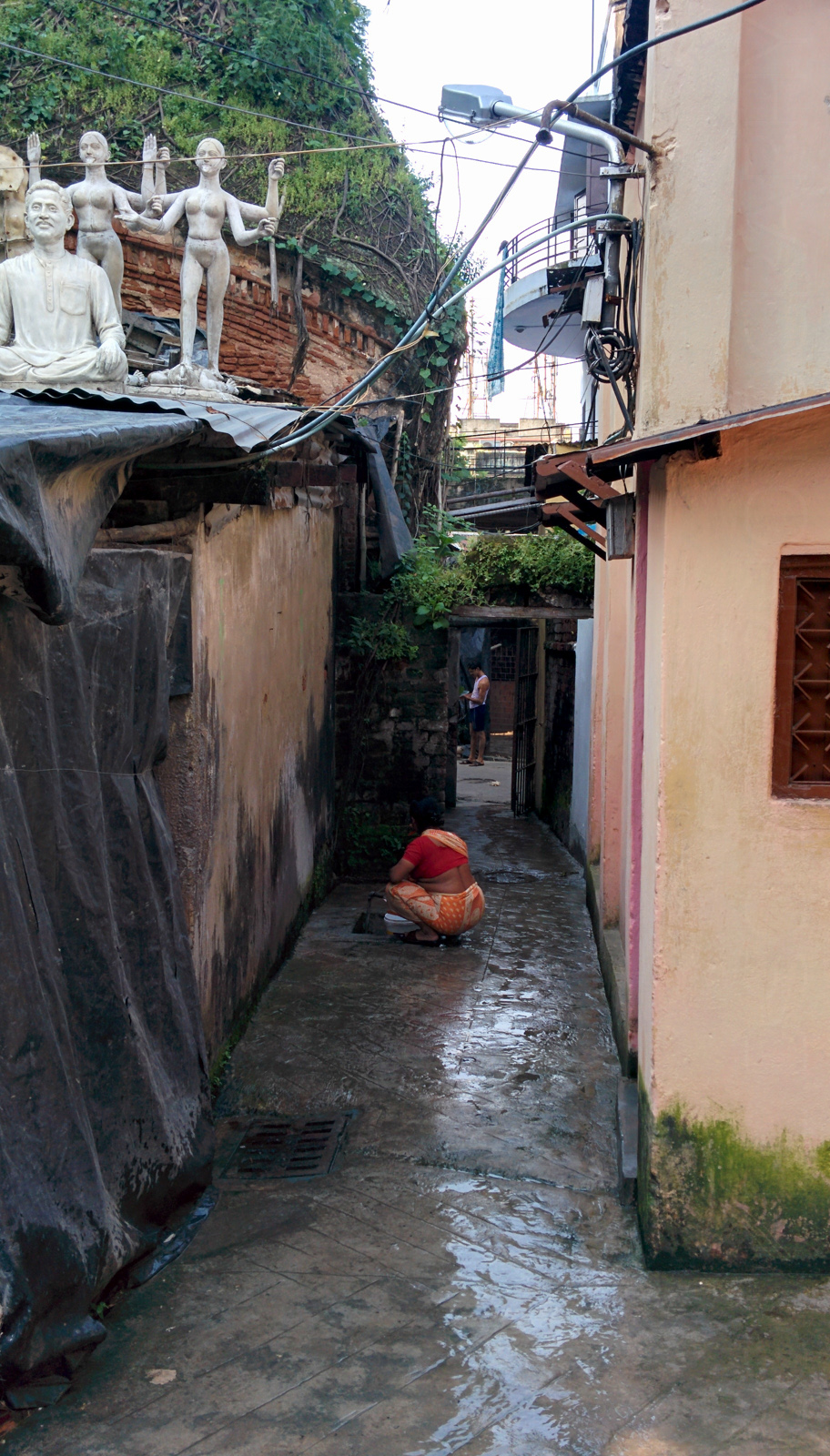 A lady washes a her clothes in the alley