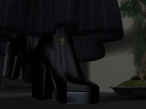 Image Description: Close-up of a pair of boots under a long skirt walking towards a bonsai tree.