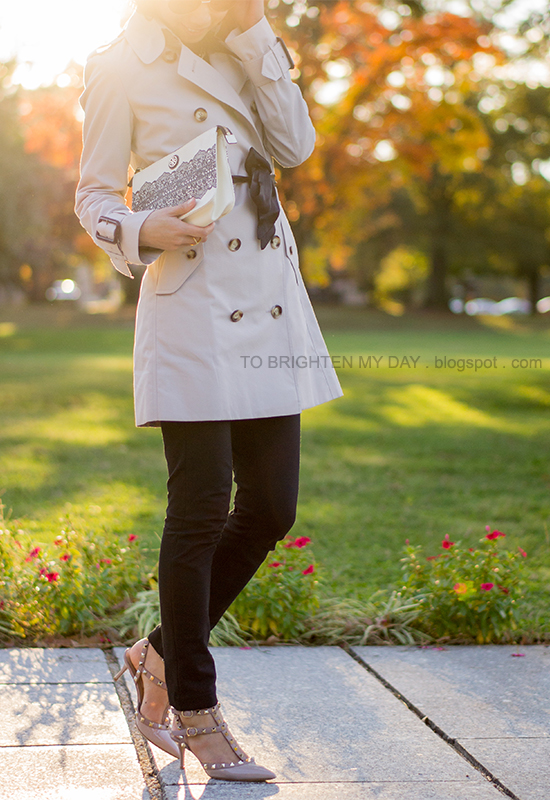 trench coat with black bow, lace clutch, studded heels