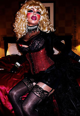 Retro diva in shiny red corset, pantyhose and stockings